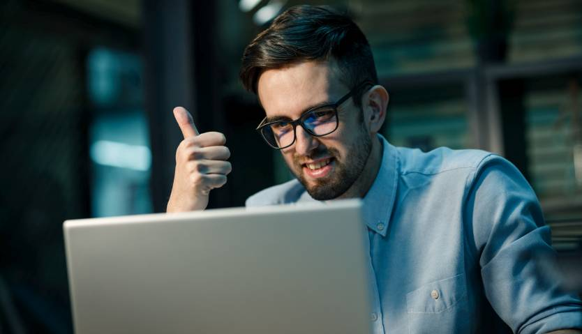 Man giving a thumbs-up and smiling while working on a laptop