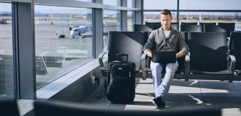 Traveler using laptop in airport terminal